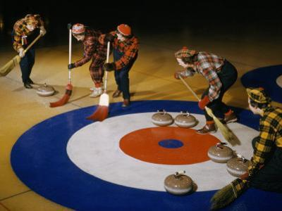 Women Sweep the Ice Ahead of a Curling Stone During a Curling Match by B. Anthony Stewart
