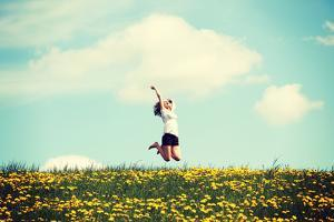 Happy Woman Jumping on Blossom Meadow. Beautiful Day on Field. by B-D-S