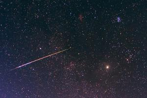 A Bright Meteor Shoots across the Sky Near Jupiter by Babak Tafreshi