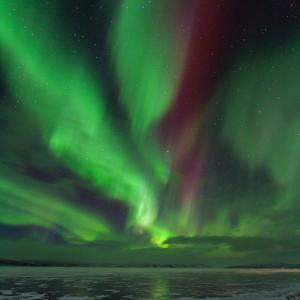 A Colorful Aurora Display over a Frozen Lake in Abisko National Park by Babak Tafreshi