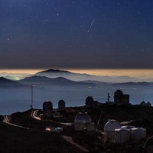 A Colorful Meteor Photographed Above Telescope Domes and Inversion Layer by Babak Tafreshi