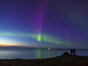 A Couple Enjoy a View of the Aurora Borealis, or Northern Lights, Above the Atlantic Ocean by Babak Tafreshi