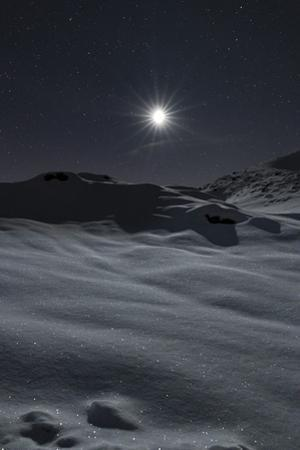 A crystal clear winter night with moonlight reflecting on snow-covered mountain landscape. by Babak Tafreshi