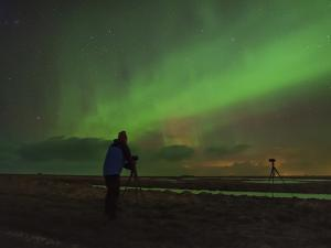 A Photographer Shooting a Green Aurora Above Farm Lands in Southern Iceland by Babak Tafreshi
