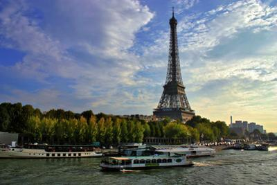 A Scenic View of the Eiffel Tower and a Ferry in the Seine River by Babak Tafreshi