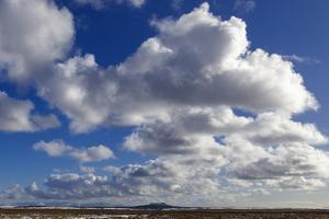 A Sunny Day in Western Iceland with Mountains and a Volcano under Fluffy Cumulus Clouds by Babak Tafreshi