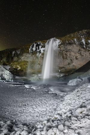 A winter night of a waterfall in Iceland with ice ball formations in the foreground. by Babak Tafreshi