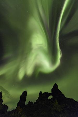 Aurora Storm, Strikingly Bright Northern Lights Dance over Black Lava Formations by Babak Tafreshi