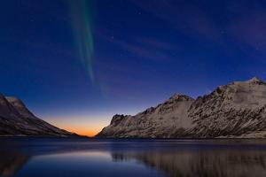 Comet Panstarrs and the Aurora Borealis Appear at Twilight over a Fjord in the Norwegian Sea by Babak Tafreshi