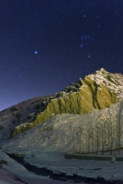 Constellations Orion and Canis Major with the Bright Star Sirius over a Snowy Mountain Landscape by Babak Tafreshi