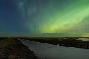 Green Aurora and Starry Sky Above a Stream Running Through Farm Lands in Southern Iceland by Babak Tafreshi