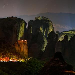 Light Shines on a Monastery Perched on a Sandstone Cliff by Babak Tafreshi