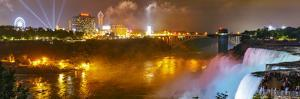 Niagara Falls Illuminated with Colored Lights, and Attractions on the Far Shore at Night by Babak Tafreshi