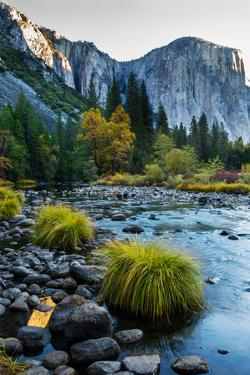 Rugged Mountains and Cliffs Along a Gentle River Filled with Boulders by Babak Tafreshi