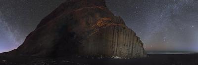 Starry sky and Winter Milky Way above basalt columns on the ocean coast. by Babak Tafreshi