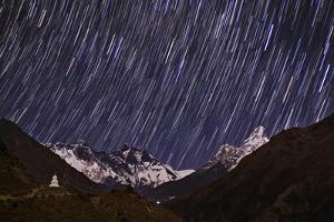 Stars Trails and Moonlit Mount Everest, Lhotse, Ama Dablam, and a Stupa by Babak Tafreshi