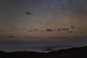 Taurus, and the Pleiades and Hyades Star Clusters at the Horizon, over the Cloud-Covered Pacific by Babak Tafreshi