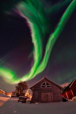 The Aurora Borealis, or Northern Lights, Appear Above a Village by Babak Tafreshi