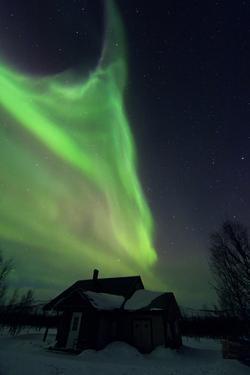 The Aurora Borealis Over a House in a Sami Village by Babak Tafreshi