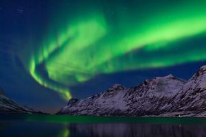The Aurora Borealis over Water and Mountains by Babak Tafreshi