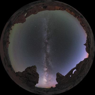 The Milky Way and fading dusk above natural Arches and rock formations in a fisheye view. by Babak Tafreshi