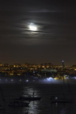 The Moon Rises Above Boats in the Bay of Cascais, Portugal by Babak Tafreshi