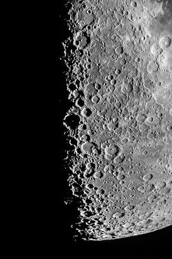 The Moon Seen Through a Telescope with Numerous Craters Along the Lunar Terminator by Babak Tafreshi