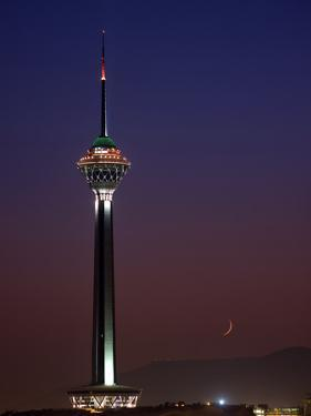 The Moon Sits in the Sky Beyond the Milad Telecommunication Tower by Babak Tafreshi