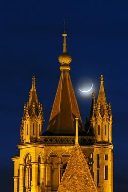 The New Moon Above the Historic Cathedral of Notre Dame, in Lausanne by Babak Tafreshi