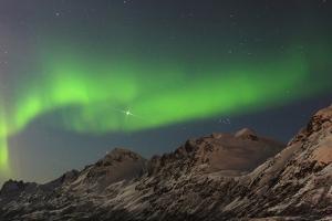 The Northern Lights, or Aurora Borealis, Dance over Rugged Mountains by Babak Tafreshi