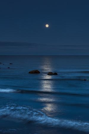 The rising full moon reflecting on the ocean at dusk with waves breaking into the shore. by Babak Tafreshi