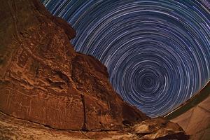 Time-Exposure of Rotating Stars Trails around the South Celestial Pole, over Atacameno Petroglyphs by Babak Tafreshi
