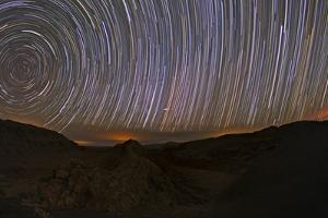 Time-Exposure of Star Trails over the Atacama Desert with the Orange Glow of Cities at the Horizon by Babak Tafreshi