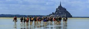 Tourists Walk the Sea Floor at Low Tide to the World Heritage Site Mont Saint Michel Monastery by Babak Tafreshi