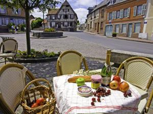 Cheese, Cherries, Apples and Champagne on Cafe Table with Half-Timbered House in Background by Barbara Van Zanten