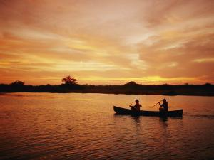 A Couple Rowing a Canoe is Silhouetted against a Gorgeous Sunset by Barry Tessman