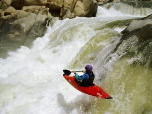 A Kayaker Careens over a Triple Drop Waterfall into the Swirling White Water Below by Barry Tessman