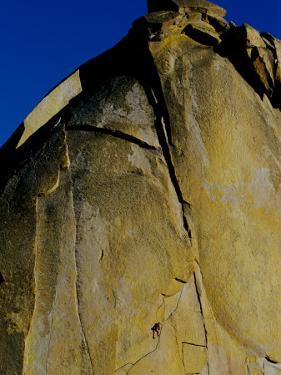 A Rock Climber Climbs a Rock Face Without the Aid of Hooks or Ropes in Needles, California by Barry Tessman