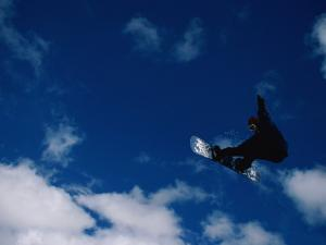 A Snowboarder Launches in the Air and Appears for a Second to Be Riding the Clouds by Barry Tessman