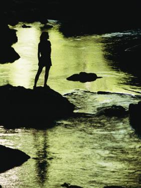 A Woman is Silhouetted Standing on a Rock Jutting out from a Stream by Barry Tessman