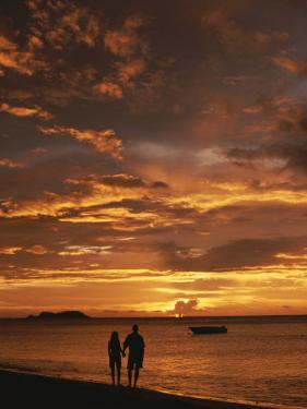 Couple Silhouetted on Beach at Twilight, Belize by Barry Tessman
