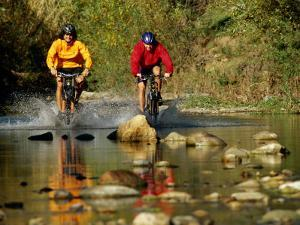 Mountain Bikers Enter a Rocky Stream by Barry Tessman