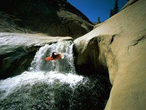 Suspended in Mid-Air, a Kayaker Sails Down a Short Waterfall and is Headed for White Water Below by Barry Tessman