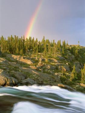 The Mist-Filled Tides of Clearwater River Wash against a Rocky Shore Where a Ra Inbow Takes Form by Barry Tessman