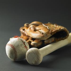 Baseball glove, a bat, and a ball