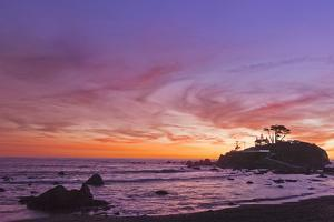 The Sun Sets Behind the Battery Point Lighthouse in Crescent City, California by Ben Coffman
