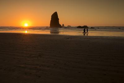 Three People Walk Along Cannon Beach, Oregon, at Sunset
