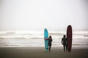 A Male And Female Surfer Hold Their Surfboards In The Olympic National Park In Washington State by Ben Herndon