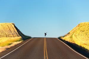Alek Engerbretson Skateboarding Down A Rural Highway Near Oakesdale, Washington by Ben Herndon