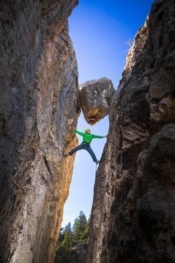 Kyle Vassilopoulos Having Fun Climbing Below A Large Chock Stone Slot Canyon At Natural Bridge SP by Ben Herndon